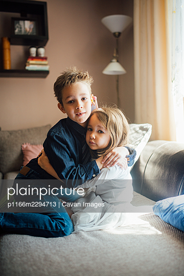 Brother and sister hugging at home. - p1166m2294713 by Cavan Images