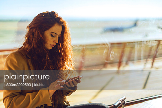 Businesswoman using smart phone by window at airport departure area - p300m2202593 by klublu