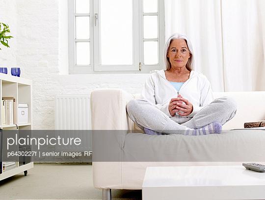 Aeltere Frau trinkt einen Kaffe auf der Couch  - p6430227f von senior images RF
