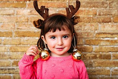 Portrait of smiling toddler girl wearing reindeer antlers headband and Christmas baubles - p300m2102968 von Gemma Ferrando