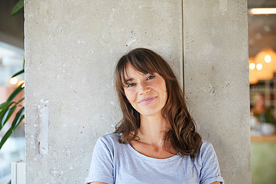 Smiling woman standing against concrete wall at home - p300m2220856 by Jo Kirchherr