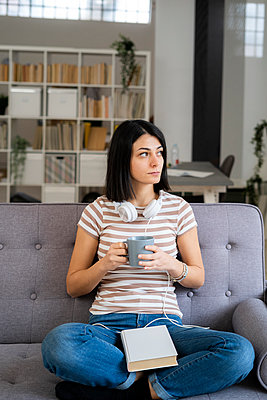 Thoughtful young woman with coffee cup sitting on sofa while looking away - p300m2266117 by Giorgio Fochesato