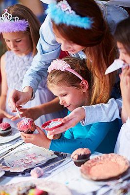 Teenage girl and girls garnishing cupcakes on a birthday party - p300m978813f by zerocreatives