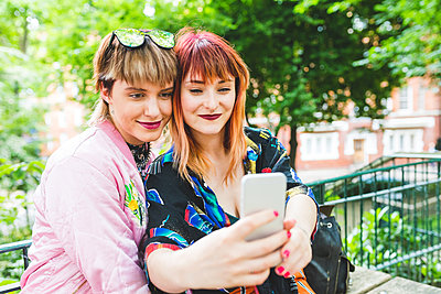 Two retro styled young women taking smartphone selfie in park - p429m1505061 by William Perugini