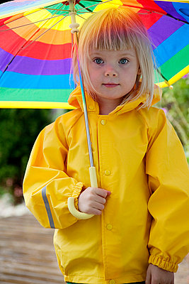 Girl standing with raincoat and umbrella - p528m718553f by Camilla Sjödin Lindqvist