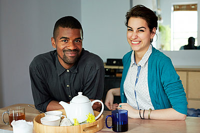 Couple smiling with tea at table - p555m1409877 by Granger Wootz