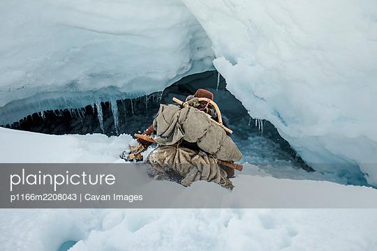 Aboriginal explorer slides down into a ice cave entrance. - p1166m2208043 by Cavan Images