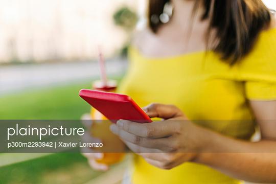 Young woman using smart phone - p300m2293942 by Xavier Lorenzo