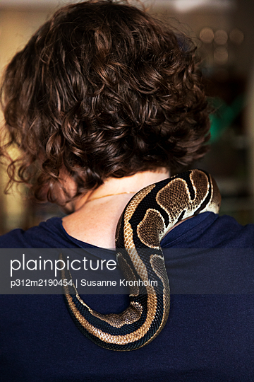 Woman with snake on shoulder - p312m2190454 by Susanne Kronholm