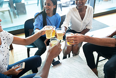Business people toasting beer glasses in office - p1023m2262104 by Himalayan Pics