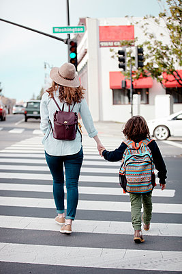 Rear view of woman holding boy's hand while crossing road in city - p1166m1403733 by Cavan Images