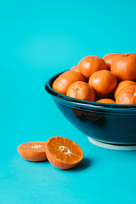 Mandarin orange cut in half by a bowl of oranges on blue background. - p1166m2094807 by Cavan Images