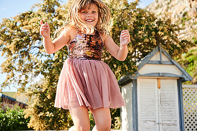 Little girl jumping on trampoline - p1640m2244883 by Holly & John