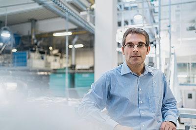 Portrait of a confident mature businessman in a factory - p300m2197787 by Daniel Ingold