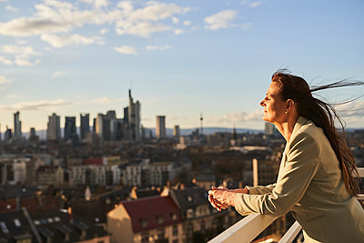 Thoughtful female entrepreneur leaning on terrace railing during sunset - p300m2281419 by Annika List
