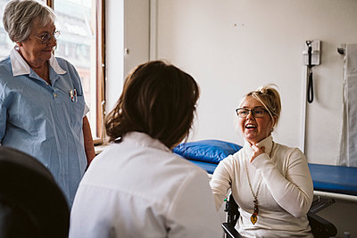 Senior female nurse looking at disabled woman consulting with doctor at medical clinic - p426m2279859 by Maskot