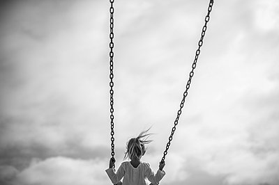 Girl on Swing Against Gray Sky, Rear View - p694m1014800 by Kristianne Riddle