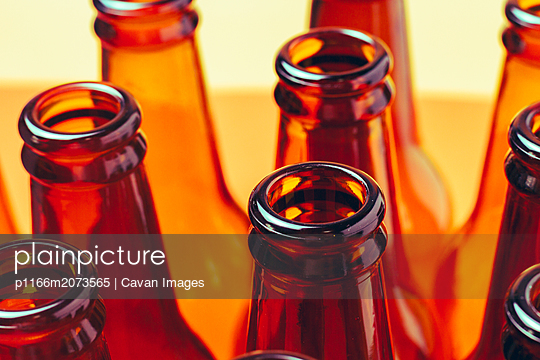 session of empty and brown glass bottles for advertising photographs - p1166m2073565 by Cavan Images