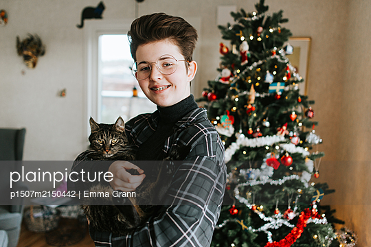 Girl with cat against Christmas tree - p1507m2150442 by Emma Grann