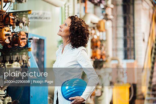 Female engineer holding hardhat while checking machine at power station - p300m2290698 by Robijn Page