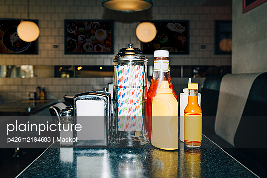 Drinking straw and bottles on table in restaurant - p426m2194683 by Maskot