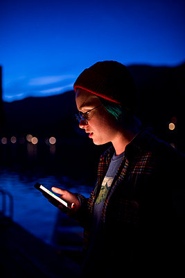 Teenage girl using mobile phone while standing against blue sky in Olympic National Park at night - p1166m2034835 by Cavan Images