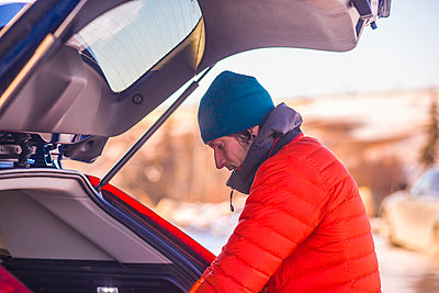 Man preparing camera gear in trunk of luxury car at sunset - p1166m2096544 by Cavan Images