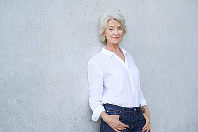 Portrait of relaxed mature woman wearing white shirt leaning against concrete wall - p300m2114974 by Philipp Nemenz