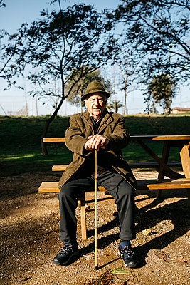 Spain, Barcelona. Retired senior man sitting on park bench leaning on his cane, looking at camera. - p300m2166539 von Josep Rovirosa