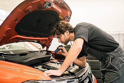 Car mechanic in a workshop working at car - p300m2166825 by Robijn Page