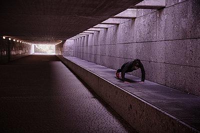 Female athlete warming up before running in pedestrian underpass - p300m2188248 by Studio 27