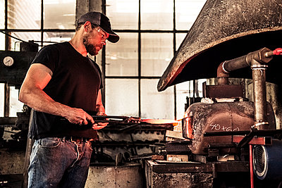 Knife maker working with damask steel at forging furnace - p300m2189595 by Wilfried Feder