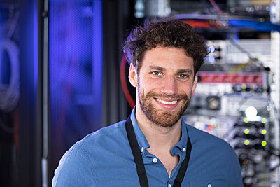 Happy male IT engineer standing in data center - p300m2275209 by Florian Küttler