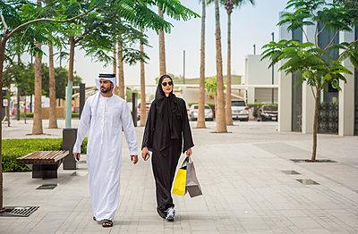 Middle eastern shopping couple  wearing traditional clothing walking along street, Dubai, United Arab Emirates - p429m1140160 by Antonio Saba