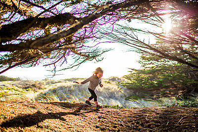 Caucasian girl running under tree branches - p555m1521334 by Adam Hester