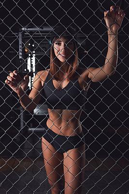Female bodybuilder behind mesh wire fence - p913m2134068 by LPF