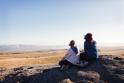 Mother and daughter looking at view while sitting on rocks against clear sky - p1166m1509666 by Cavan Images