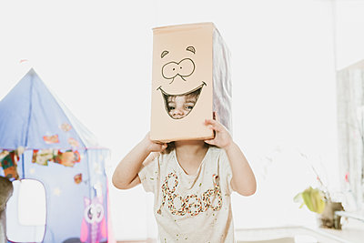 Portrait Of Playful Girl With Cardboard Box On Head At Home - p1166m2136856 by Cavan Images