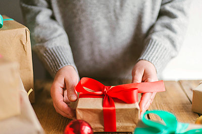 Woman wrapping christmas gifts on wooden background - p1166m2153796 by Cavan Images