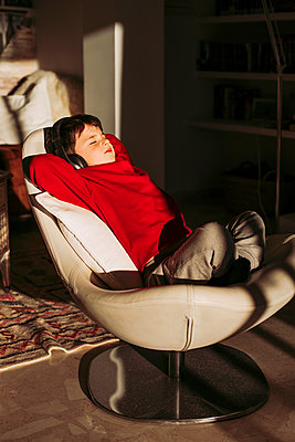 Boy listening music through headphones while relaxing on chair at home - p300m2266641 by DREAMSTOCK1982