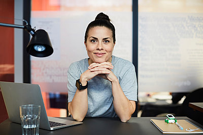Portrait of confident creative businesswoman sitting at desk in office - p426m2074587 by Maskot