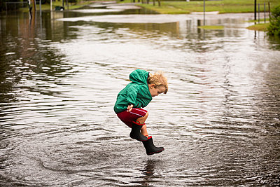 Caucasian boy jumping in puddle - p555m1311553 by Roberto Westbrook