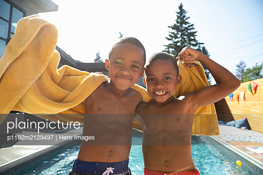 Portrait cute, carefree twin brothers flexing muscles at sunny, summer poolside - p1192m2129497 by Hero Images