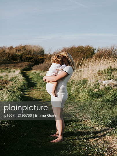 Pregnant woman carries toddler in her arms - p1507m2195786 by Emma Grann