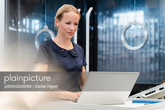 Smiling female entrepreneur working on laptop at industry - p300m2240084 von Daniel Ingold