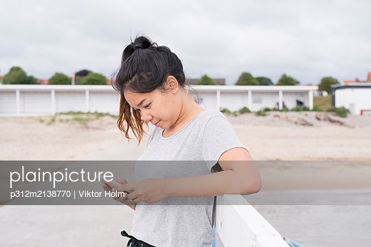 Young woman using cell phone - p312m2138770 by Viktor Holm