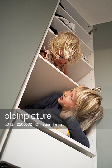 Sisters sitting on shelves in wardrobe - p312m2208092 by Christian Ferm