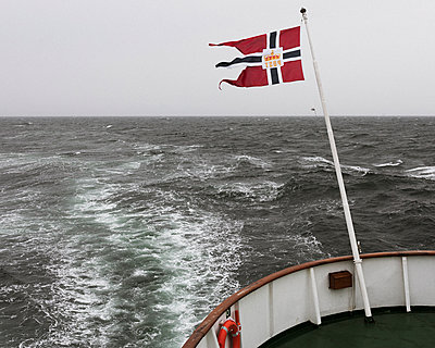 Flag flies on the stern of the ship in heavy seas - p1214m2263140 by Janusz Beck