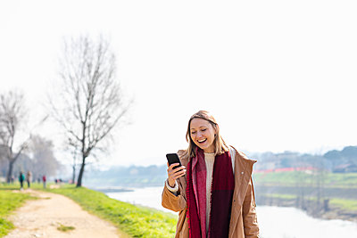 Happy woman using mobile phone - p300m2274322 by Emma Innocenti