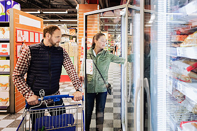 Couple buying groceries while standing at refrigerated section - p426m1148152 by Maskot